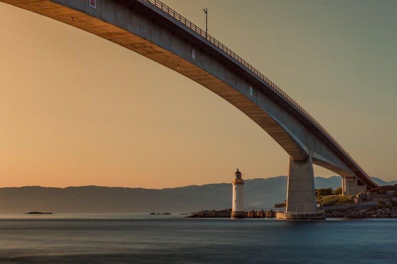 Ponte sul mare con un faro.